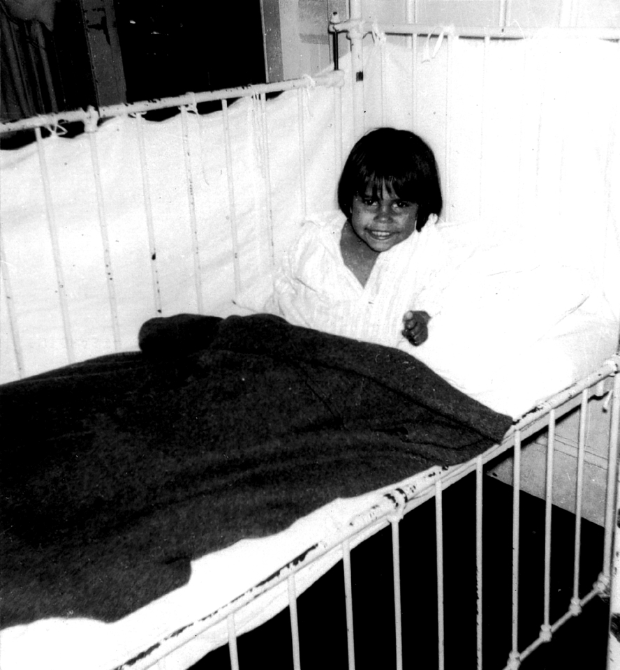 Child in bed at Cherbourg Hospital c1961