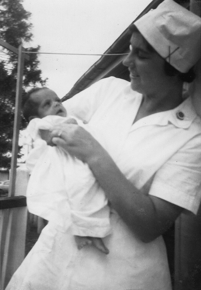 Nurse holding a baby at Cherbourg Hospital c1961