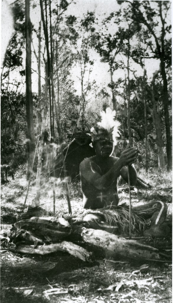 Decorated man with fire sticks at Barambah Aboriginal Settlement c1920