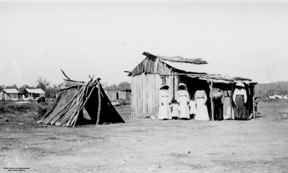 Group and huts at Barambah Aboriginal Settlement 1911