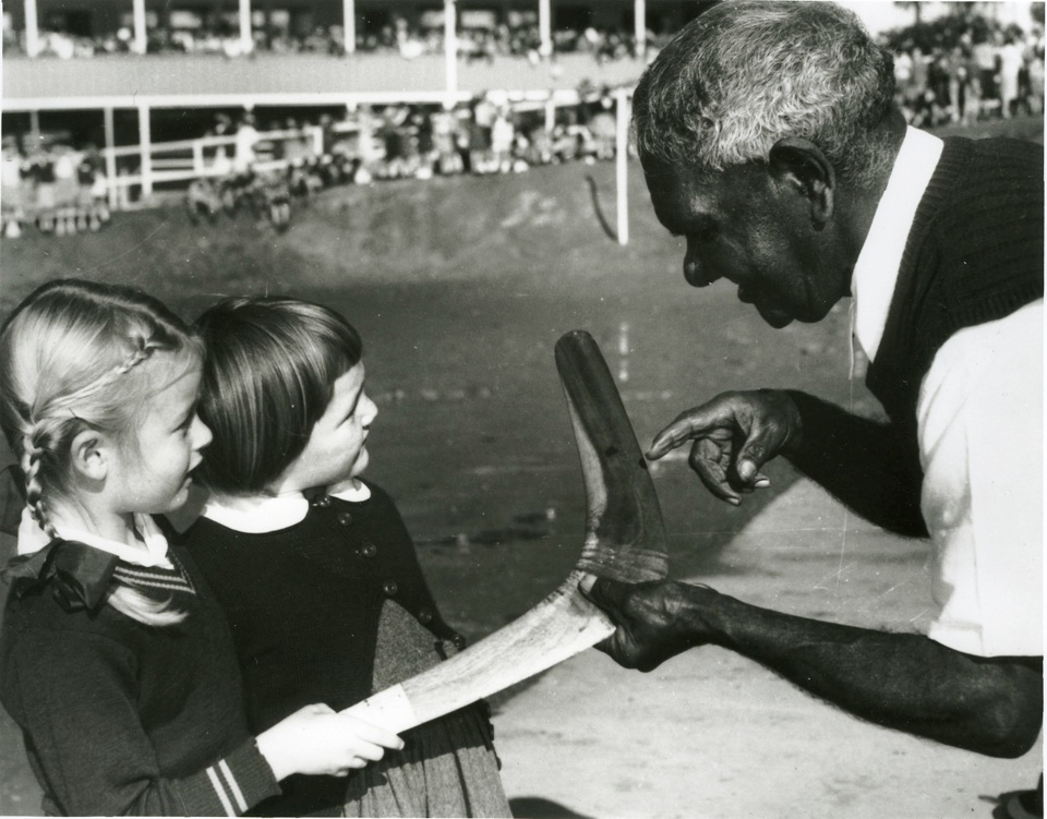 Willie McKenzie with boomerang talking to girls c1940