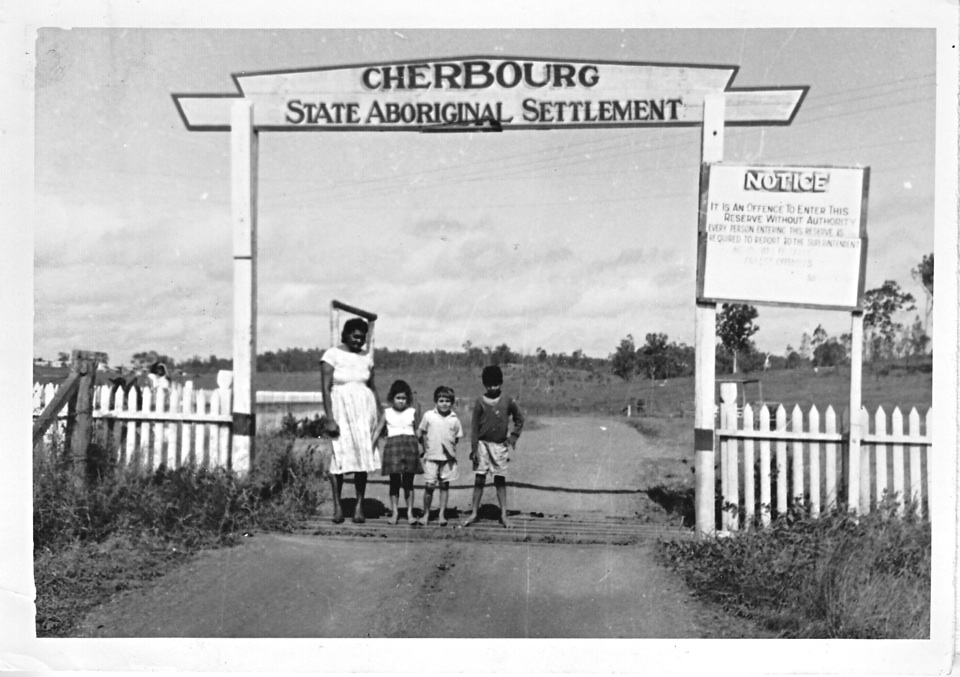 May Mathieson with her grandchildren at the entrance to Cherbourg State Aboriginal Settlement 1962