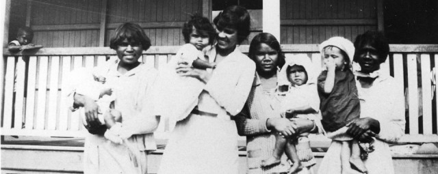 Women with children in front of girls dormitory at cherbourg