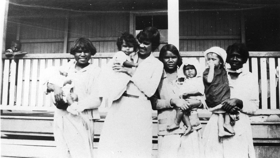 Women with children in front of Girls Dormitory at Cherbourg Aboriginal Settlement c1930